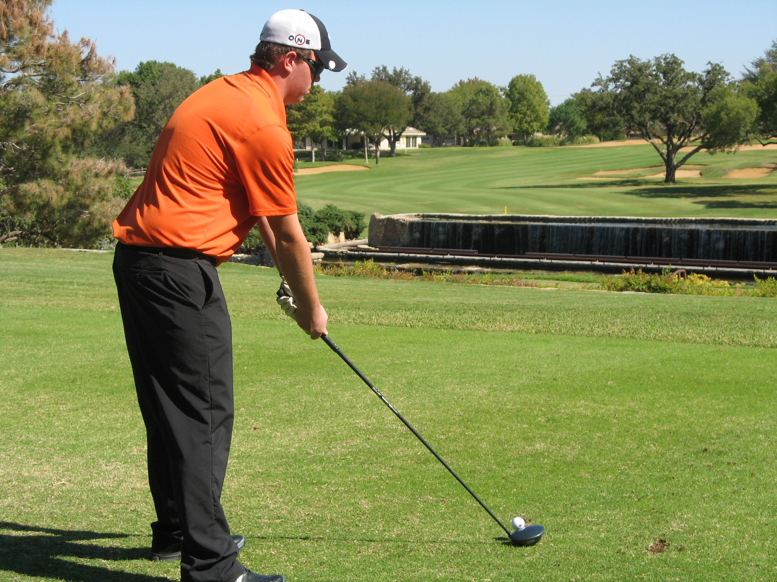 Golfer in an orange shirt about to take a swing